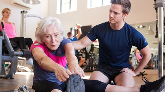 elderly woman exercising with trainer